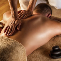 Man has deep tissue massage on the back. Spa stones and frangipani flowers.